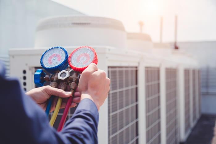 technician checking air conditioner measuring equipment sm